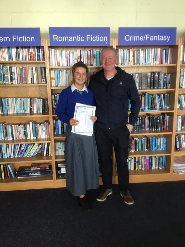 Desmond College students in School Library with family, delighted with their results